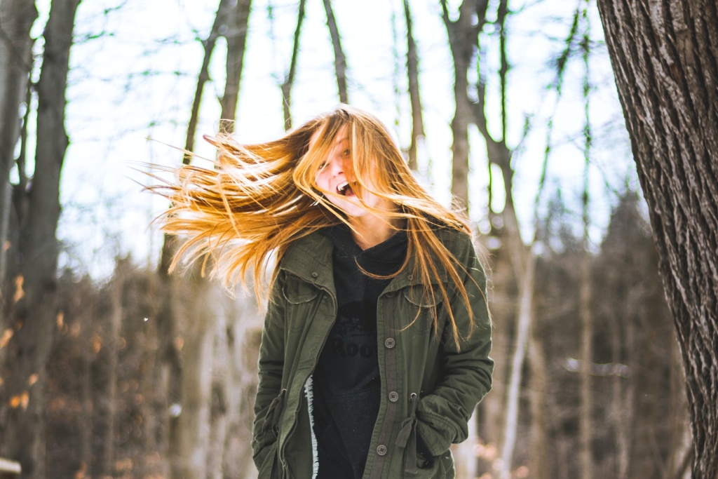 Woman walking in woods in winter - being out in natural light is important for managing Seasonal Affective Disorder (SAD)