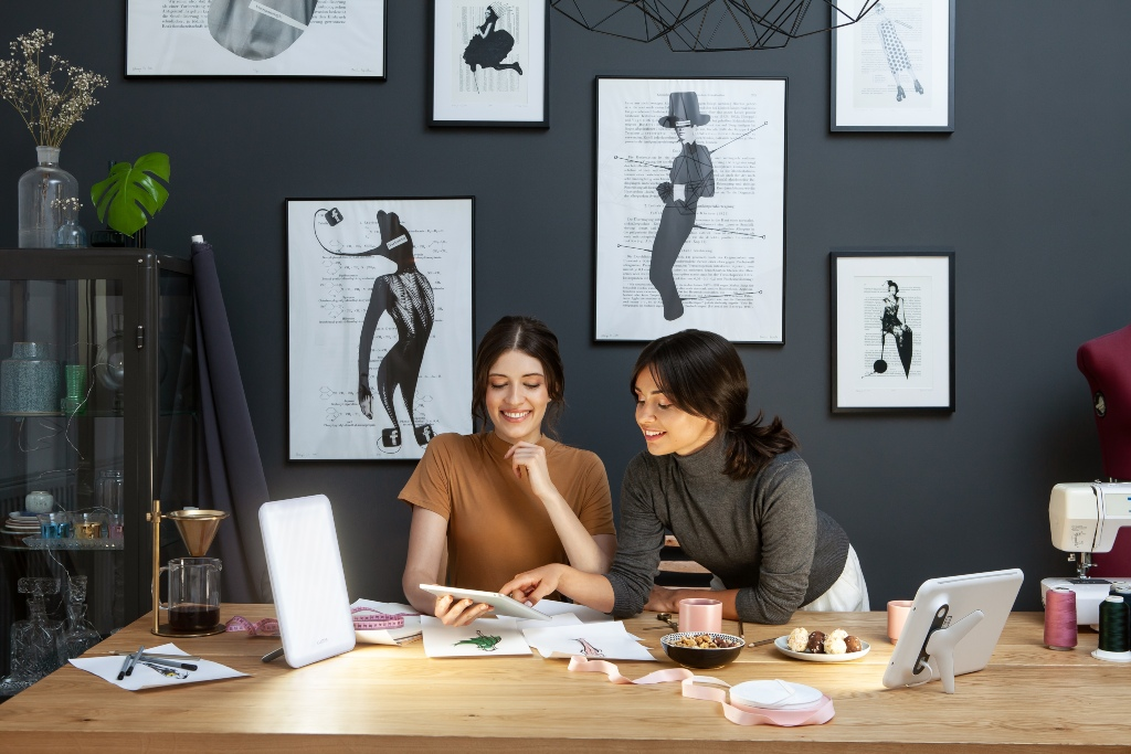 Two female creatives working in front of two Lumie Vitamin L lights receiving bright light therapy