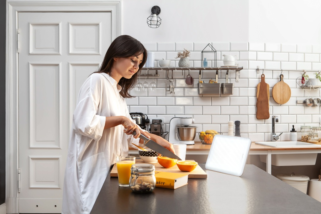 Woman cutting fruit in kitchen in front of a Lumie Vitamin L SAD light