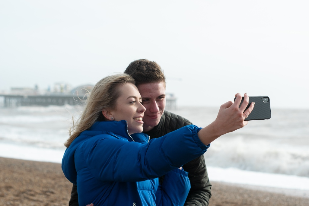 Couple taking a selfie with a mobile phone on a beach