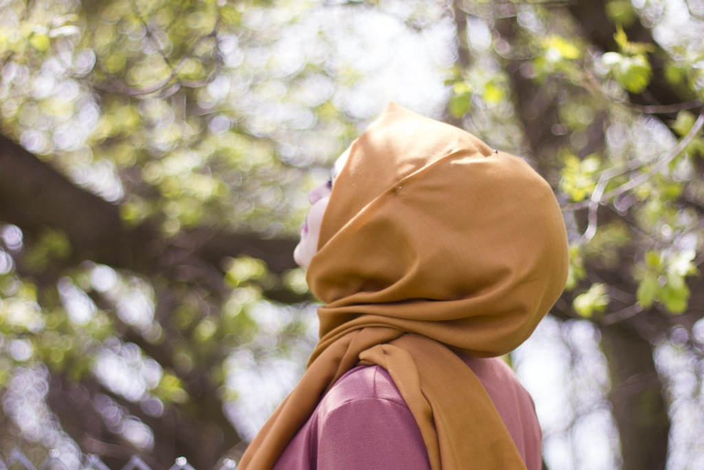 lady wearing a hijab taking an outdoor walk tilting her face up to the sunshine